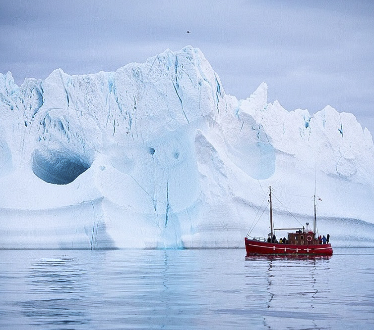 Tourists on a boat tour sailing by a giant iceberg near Ilulissat in North Greenland