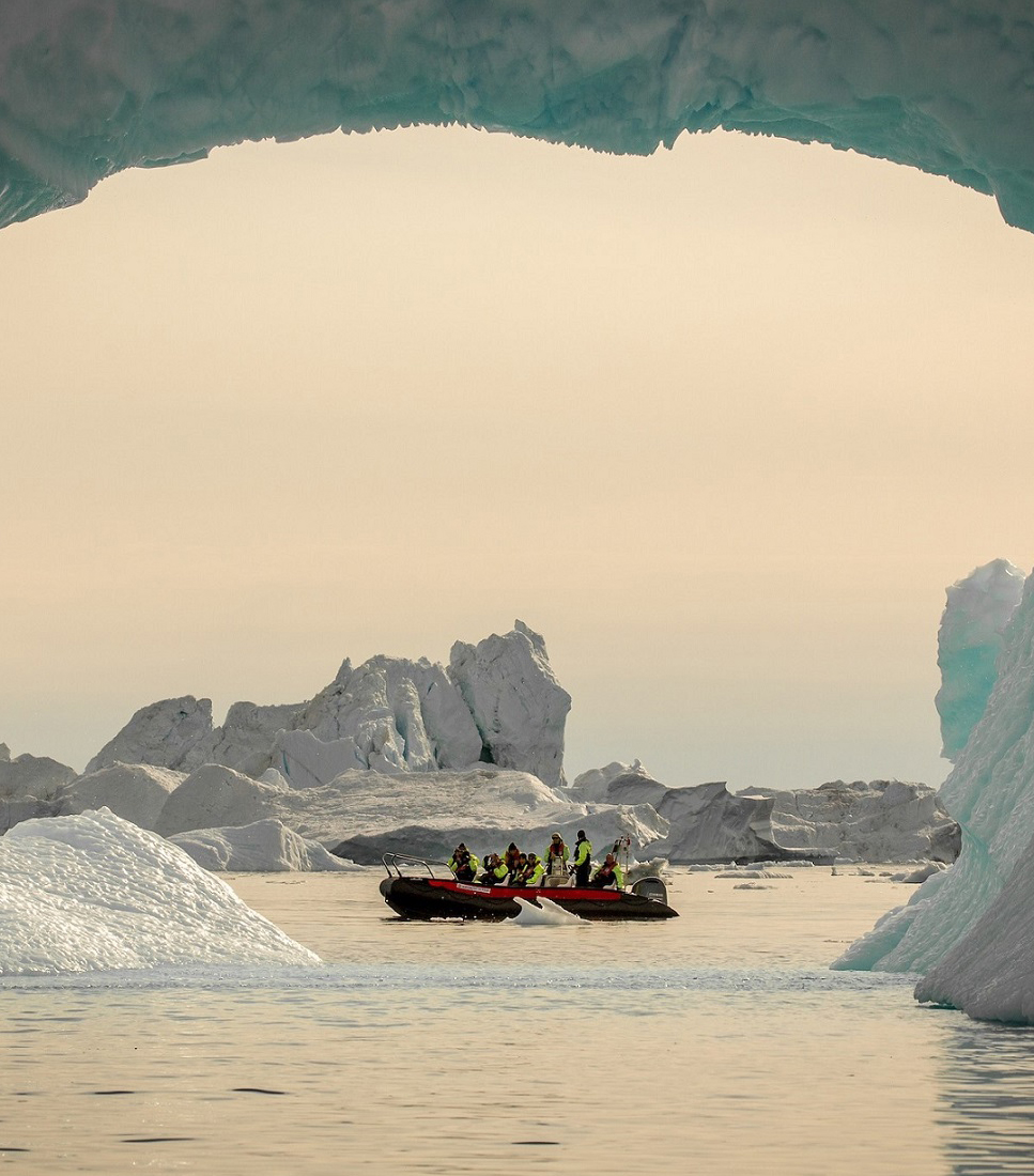 A small boat seen through an iceberg arc in the Disko Bay in Greenland